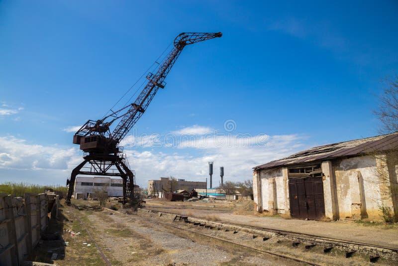Oude roestige kraan op verlaten industriezone stock fotografie
