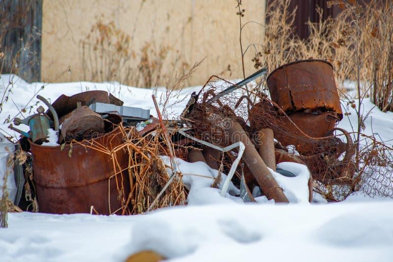 Oude roestige metaalstortplaats in de sneeuw stock foto
