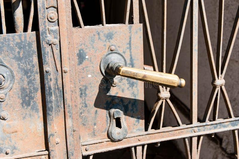 Oude roestige omhoog geschoten het handvat dicht van de ijzerdeur stock afbeelding