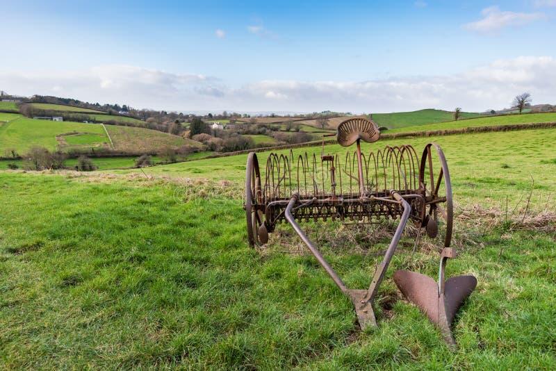Oude roestige paard getrokken hooihark op een grasgebied met Devonshire-platteland en heuvels op de achtergrond royalty-vrije stock foto's