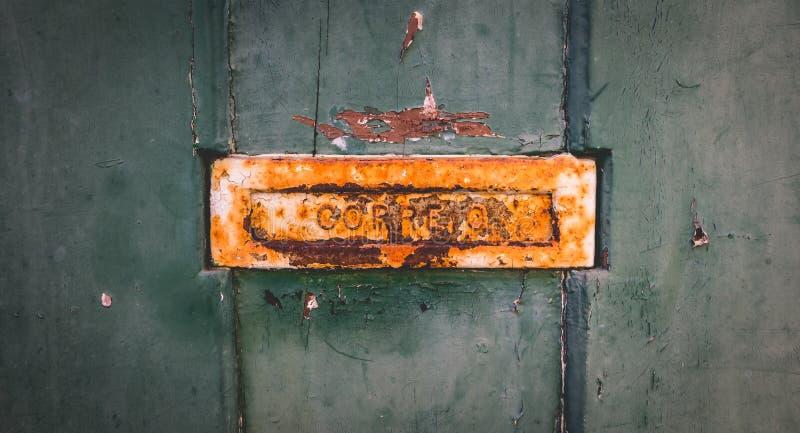 Oude roestige Portugese brievenbus op een versleten houten deur royalty-vrije stock fotografie