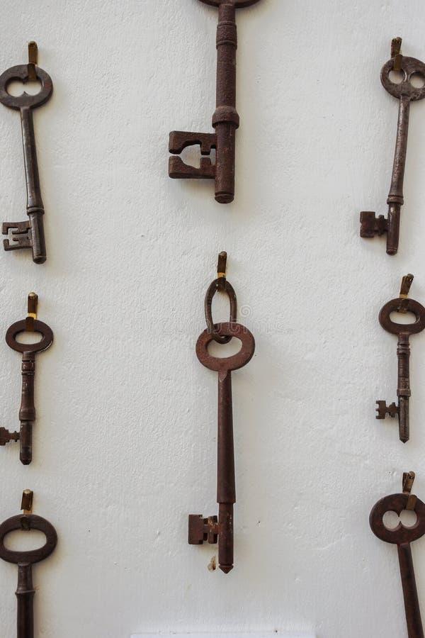Oude roestige sleutels die op een witte muur hangen stock afbeeldingen