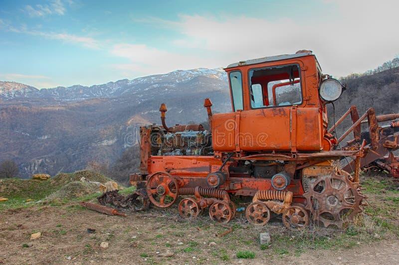 Oude roestige tractor op de achtergrond van bergen stock foto's