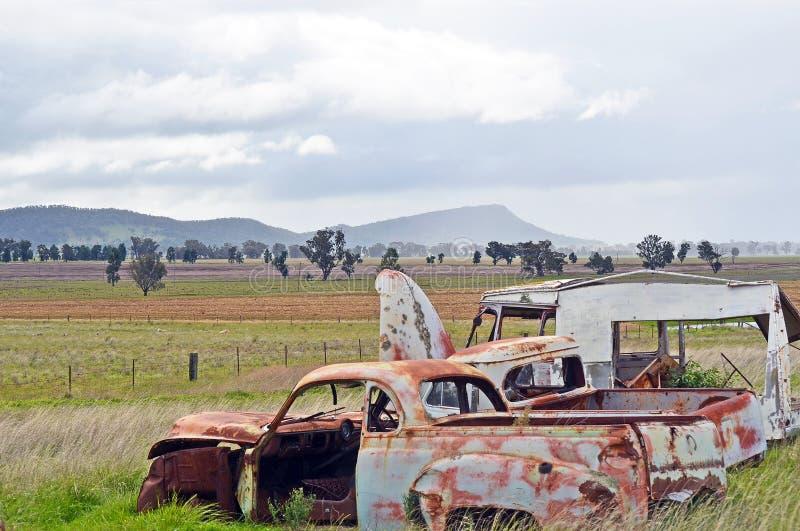 Oude roestige, verlaten uitstekende auto's in het platteland stock afbeeldingen