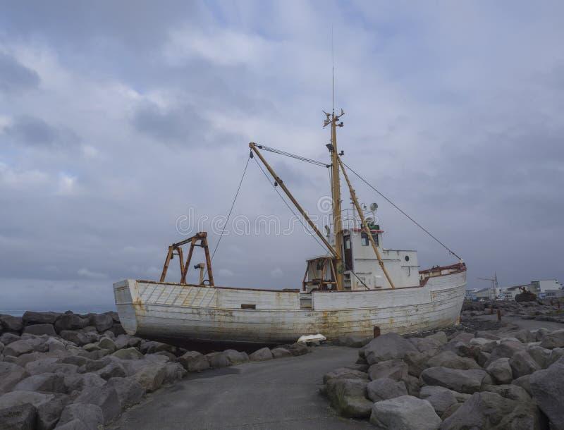 Oude roestige verlaten vissersboot, schipwrak die zich op rots, s bevinden stock foto's
