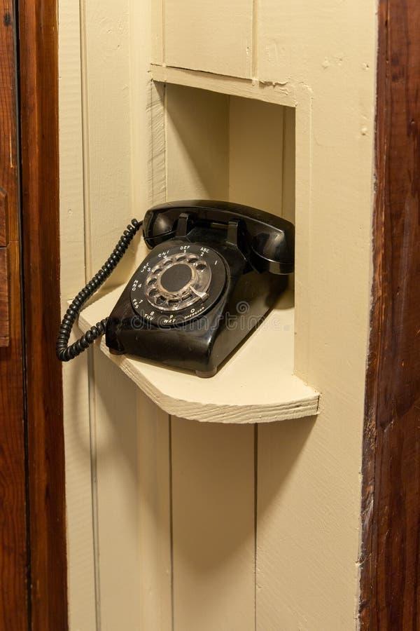 Oude Roterende Telefoonzitting in hoekje in gang stock foto