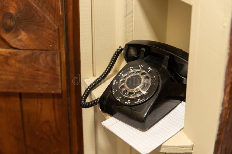 Oude Roterende Telefoonzitting in hoekje in gang stock foto's