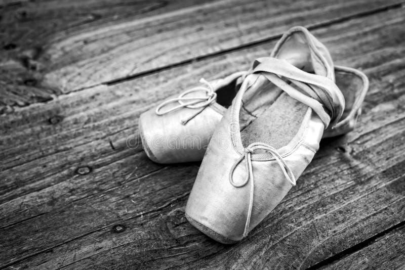 Oude roze balletschoenen op een houten vloer royalty-vrije stock foto