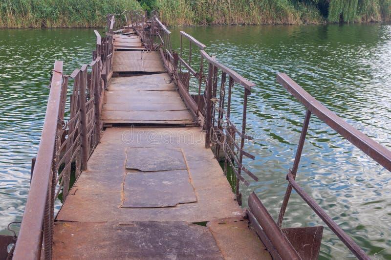 Oude, roze pontoon-brug over de kleine rivier Sura naar afgelegen Oekraïens dorp stock foto