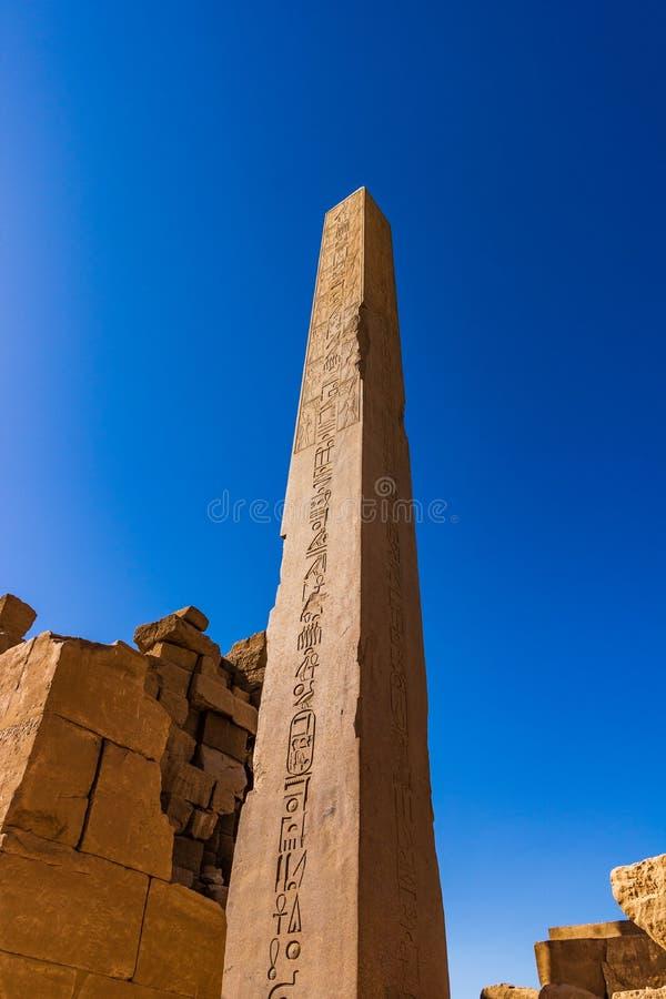 Oude ruïnes met een obelisk met hiërogliefen op de blauwe hemelachtergrond in Luxor in Egypte stock afbeeldingen