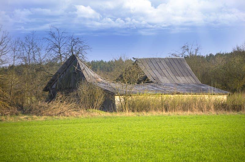 Oude ruïnes van schuur met gebroken dak stock afbeelding