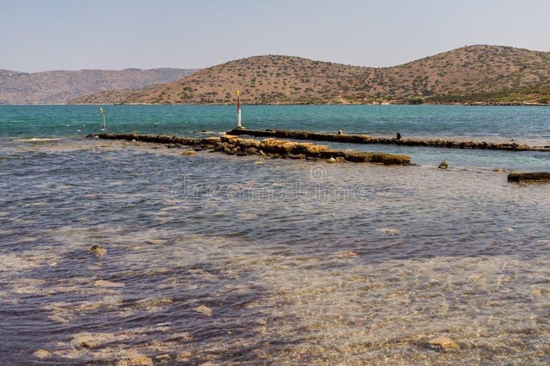 Oude ruïnes van windmolen en haven in Elounda-stad, het eiland van Kreta, Griekenland stock afbeeldingen