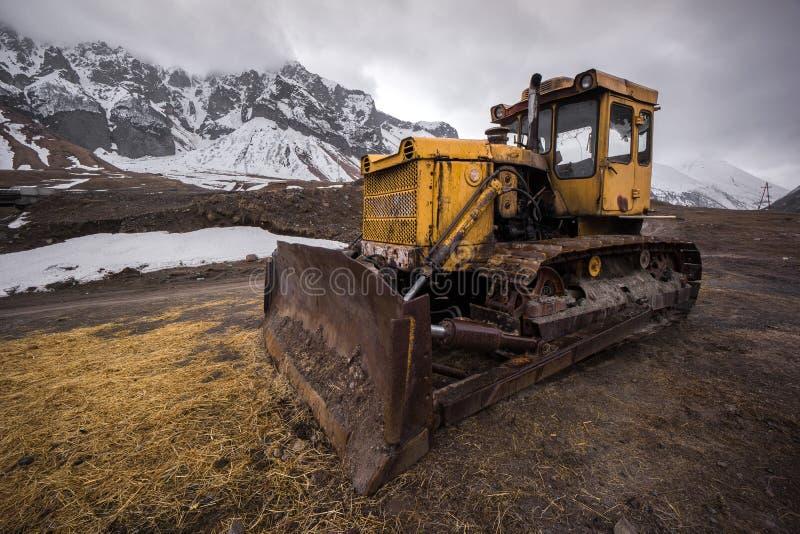 Oude Russische bulldozer in kazbegi stock foto's