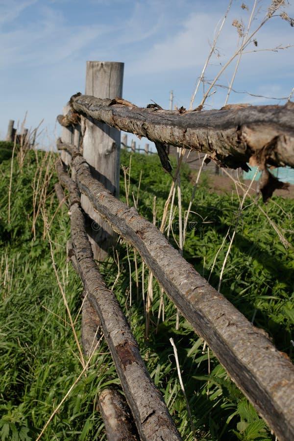 Oude rustieke houten omheining in het Siberische dorp, die zich in de afstand uitrekken stock afbeelding