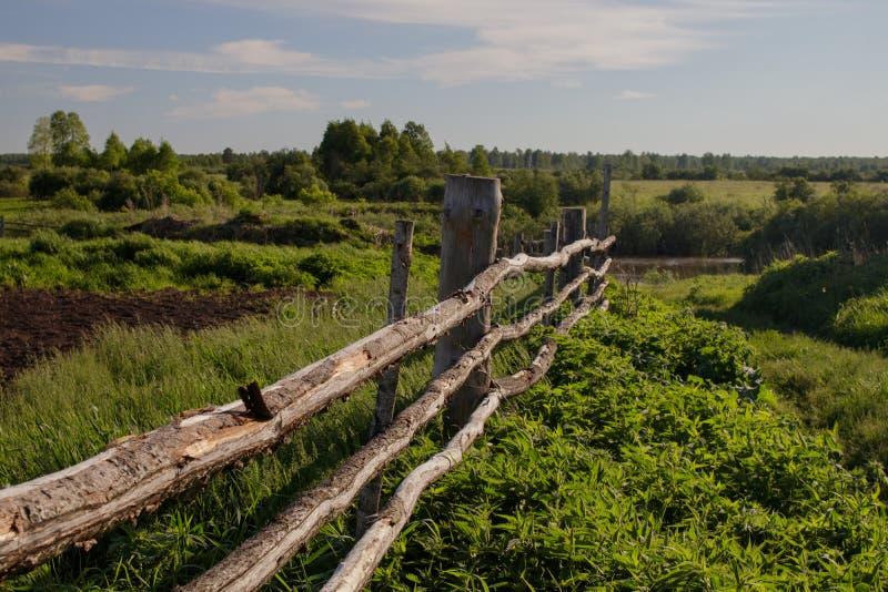Oude rustieke houten omheining in het Siberische dorp, die zich in de afstand uitrekken royalty-vrije stock foto