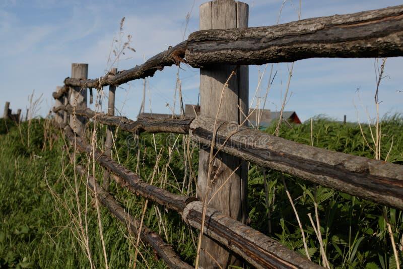 Oude rustieke houten omheining in het Siberische dorp, die zich in de afstand uitrekken stock foto's