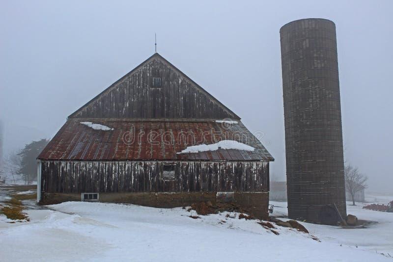 Oude rustieke schuur en silo in de winter stock afbeelding