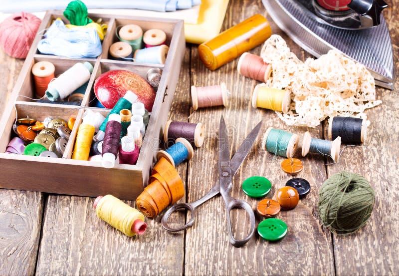 Oude schaar, diverse draden, ijzer en naaiende hulpmiddelen stock fotografie