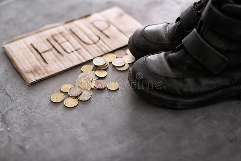 Oude schoenen, muntstukken en stuk van karton royalty-vrije stock afbeelding