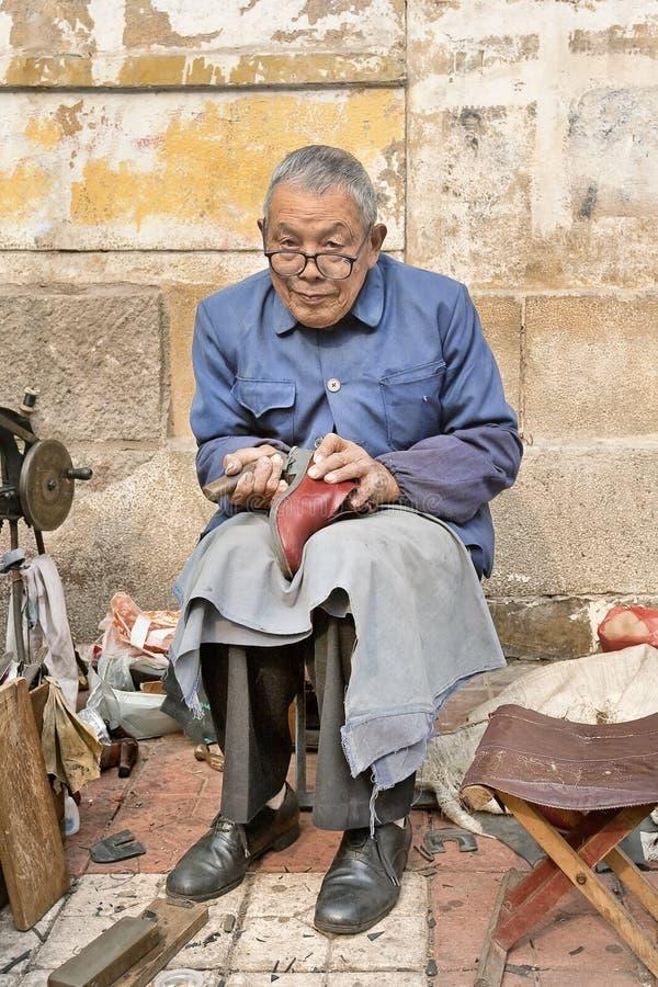 Oude schoenmaker op de straat, Peking, China stock fotografie