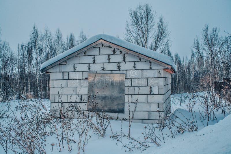 Oude schuur grijze concrete muur met sneeuw op het dak en ingescheept op het venster stock foto's