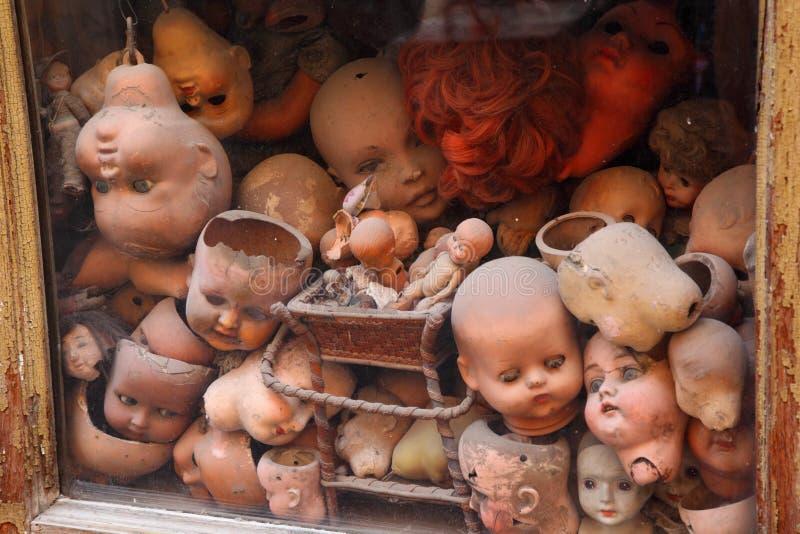Oude showcase met vele oude hoofdenpoppen stock foto