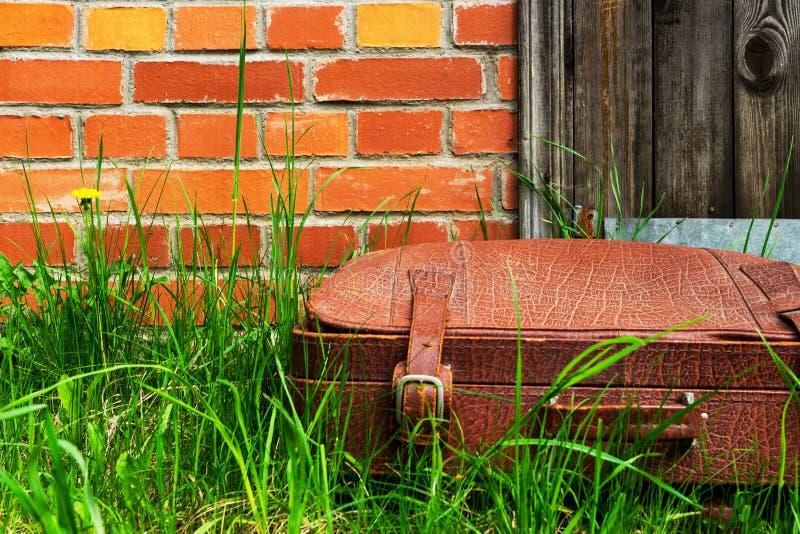 Oude sjofele koffer in het gras, tegen een bakstenen muur royalty-vrije stock afbeelding