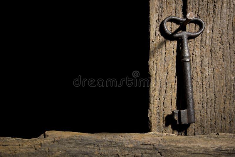 Oude sleutel op een logboek stock foto