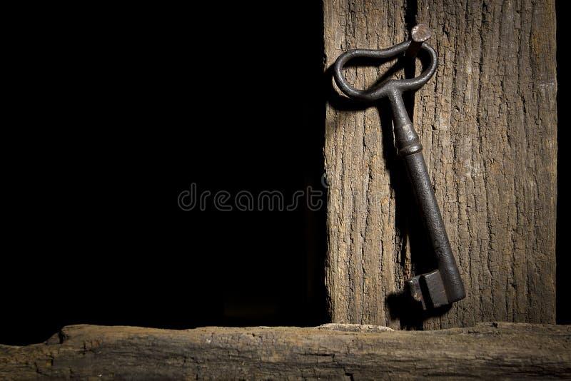 Oude sleutel op een logboek stock fotografie