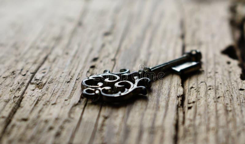 Oude sleutel tot uw bruin hout van de hartliefde stock foto