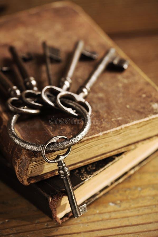 Oude sleutels op een oud boek stock fotografie