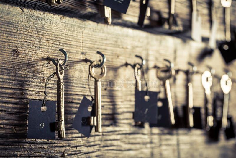 Oude sleutels voor hotelruimten op houten muur royalty-vrije stock foto