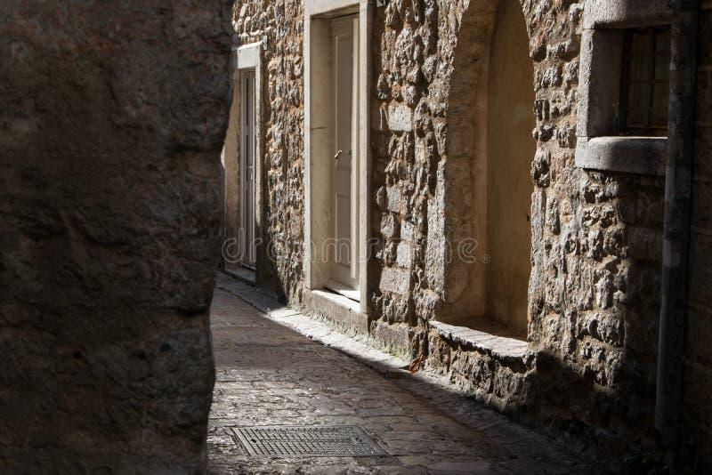 Oude smalle straat en steengebouwen in de oude stad van Budva royalty-vrije stock fotografie