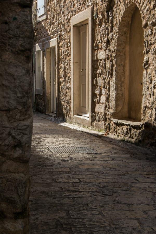 Oude smalle straat en steengebouwen in de oude stad van Budva stock afbeelding