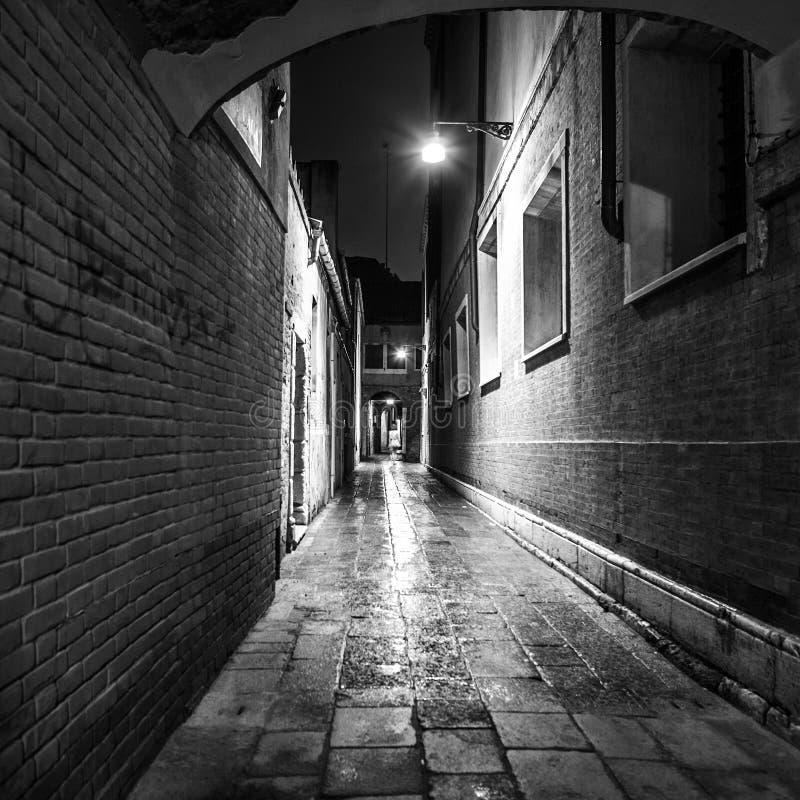 Oude smalle straten en voorgevels van oude middeleeuwse gebouwen bij nachtclose-up Venetië, Italië stock fotografie