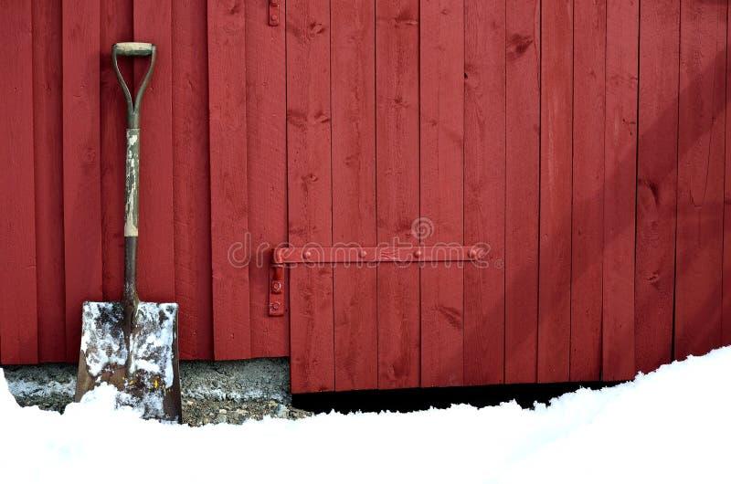 Oude sneeuw die showel op rode schuurmuur rusten in de sneeuwwinter stock afbeeldingen