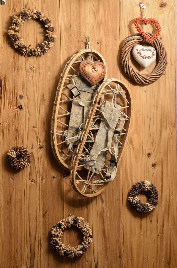 Oude Sneeuwrackets op Houten Muur met Kronen en Slingers in Mou stock fotografie