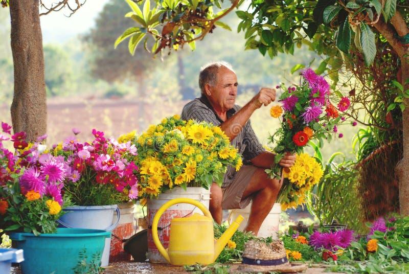 Oude Spaanse landbouwer die de bloemstukken van het land maken