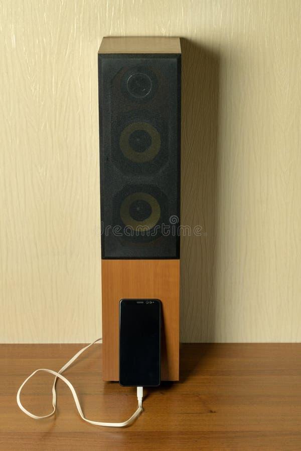 Oude spreker die door USB-kabel met smartphone wordt verbonden Het concept van de vooruitgangstechnologie stock foto's