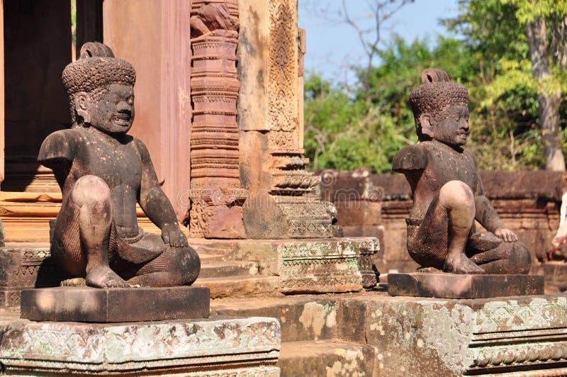 Oude standbeelden dichtbij de deur in de tempel Banteay Srei royalty-vrije stock foto