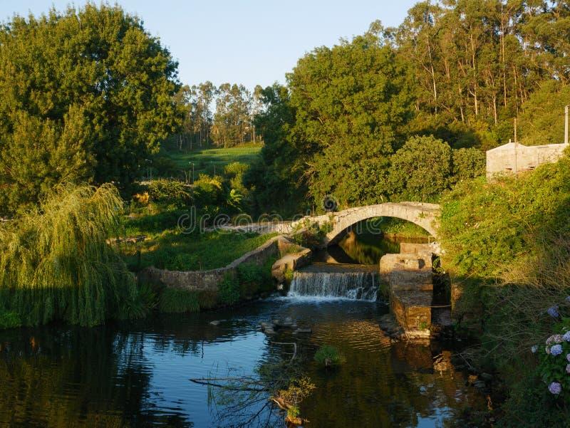 Oude, steen Roman brug over Rivier Este in Vila do Conde, Portugal bij zonsondergang stock foto's