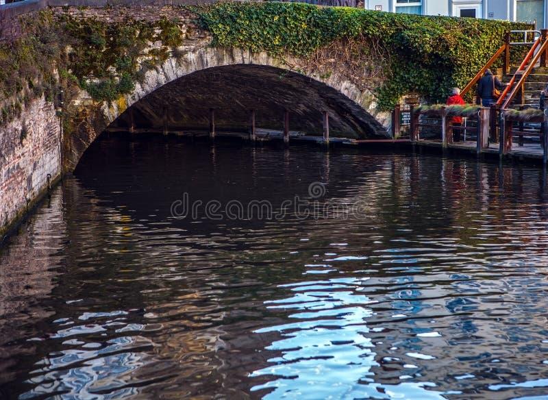 Oude steenbrug door rivier in Brugge, België stock afbeeldingen