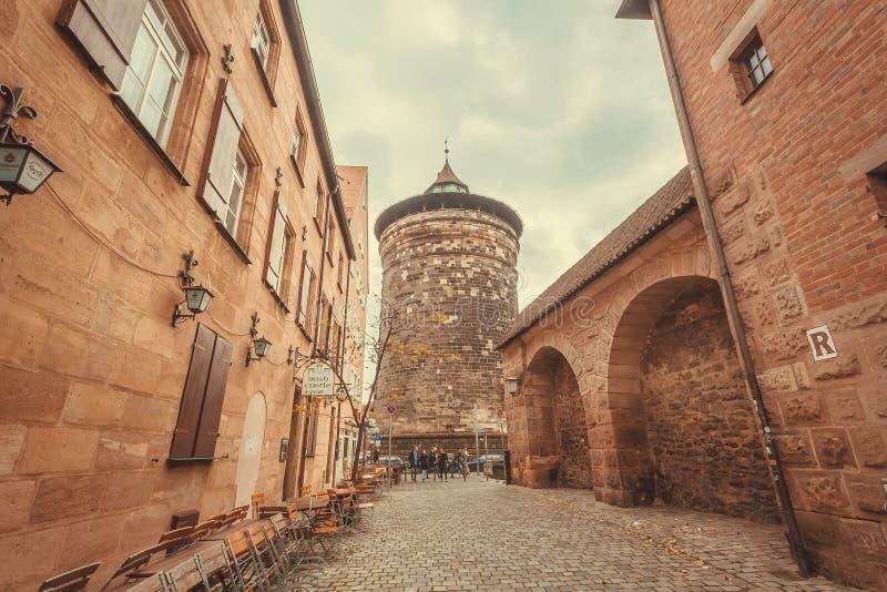 Oude steentoren binnen historische stad met baksteenhuizen en grunge muren stock afbeeldingen