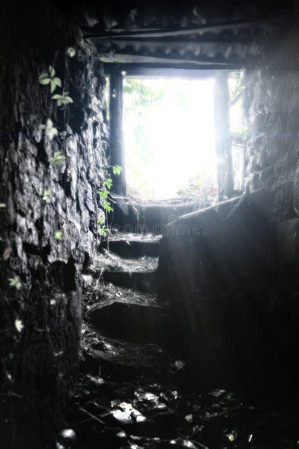 Oude steentrap om de ondergrondse kelder te verlaten Licht aan het eind royalty-vrije stock afbeelding