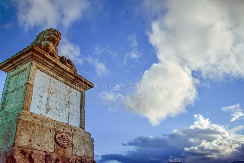 Oude stenen randverkeersteken met een blauwe hemel en wolken royalty-vrije stock foto's