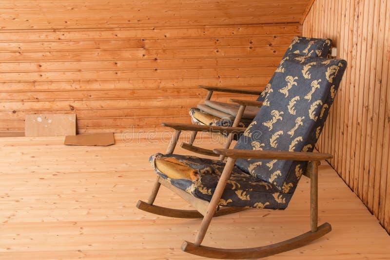 Oude stoelen voor wederopbouw Twee oude schommelstoelen op een portiek stock foto