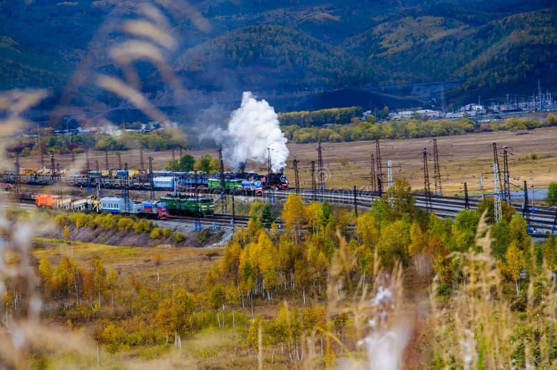 Oude stoomlocomotief in de Spoorweg circum-Baikal met rook in de herfst stock foto