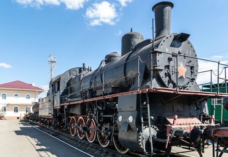 Oude stoomlocomotief naast een stationplatform Retro trein royalty-vrije stock afbeelding