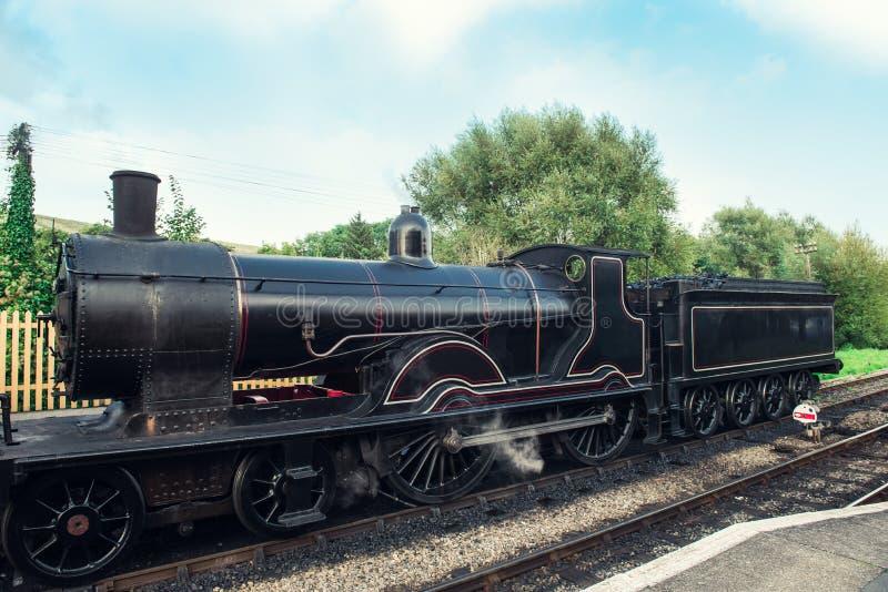 Oude Stoomlocomotief op spoorwegpost De uitstekende weg van de Stoomspoorweg Oude Locomotief op post Britse spoorreis Uitstekende stock afbeeldingen