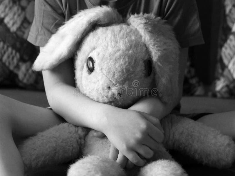 Oude stuk speelgoed hazen in de zwart-witte handen van kinderen, royalty-vrije stock afbeeldingen